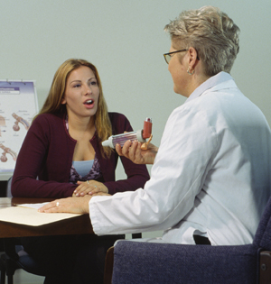 Woman sitting at desk with healthcare provider. Healthcare provider is showing woman metered-dose inhaler.