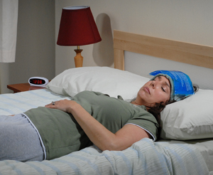 Woman lying on bed resting with cold compress on forehead.