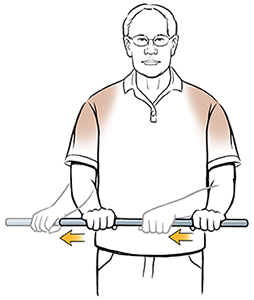 Man standing doing external rotation shoulder exercise with wand.