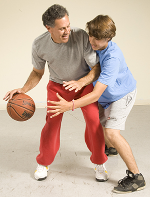 Man and teenage boy playing basketball.