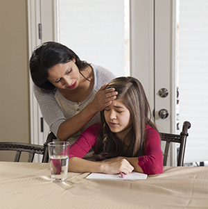 Teen girl doing homework, woman feeling her forehead.