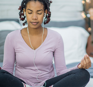 Woman seated with her eyes closed, legs crossed, meditating