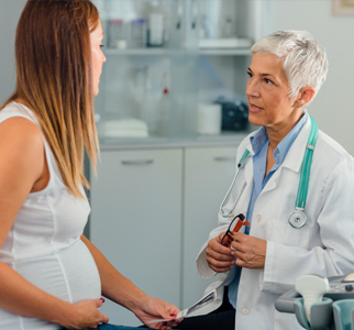 Healthcare provider talking with pregnant woman in an exam room