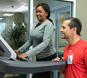 Woman on treadmill being coached by physical therapist.