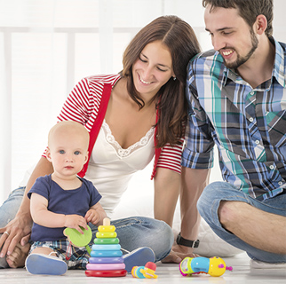 Parents sitting on the floor watching their baby playing with baby safe toys.