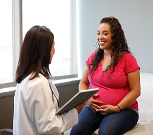 Pregnant woman in exam room talking to healthcare provider.