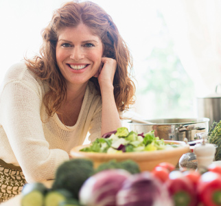 Woman smiling and bending over a bowl filled with a green salad