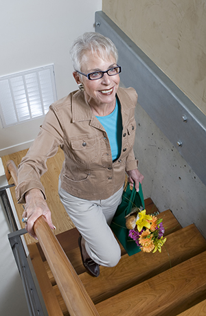 Woman walking up stairs with flowers.