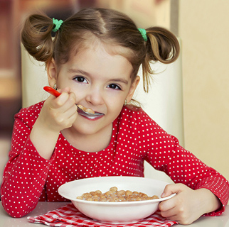 Three year old girl eating breakfast at a table.